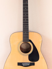 Acoustic guitar on orange wall background