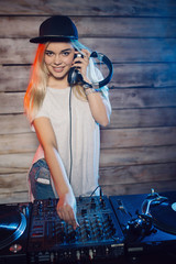 Cute dj woman having fun playing music at club party