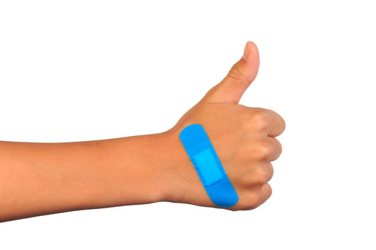 Hand making thumbs up sign with adhesive bandage on