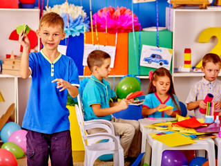 Group kids with colored paper on table in start school.