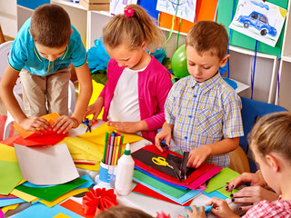 Group kids holding colored paper on table in preschooler.