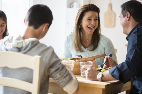 Caucasian family laughing and eating at table