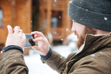 Man taking pictures with cell phone in snowy weather