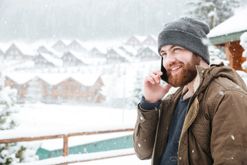 Smiling man talking on cell phone outdoors in snowy weather