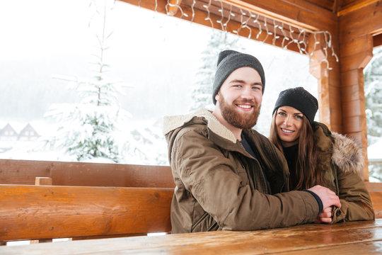 Couple sitting together at the wooden table on chalet patio