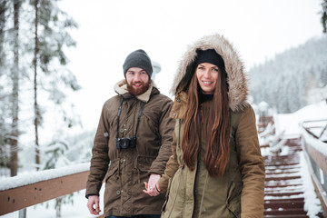Couple holding hands and walking down the stairs in winter
