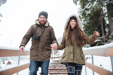 Couple holding hands and running down the stairs in winter