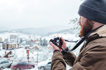 Bearded  man taking pictures of view outdoors in winter