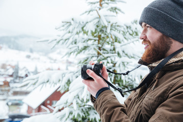 Focused man using camera and taking photos in winter