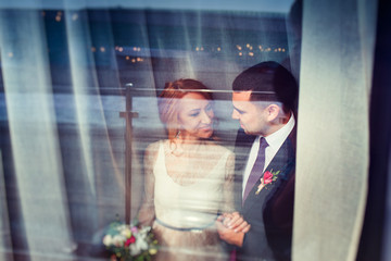 Wedding couple - bride and groom at the reflection of the window