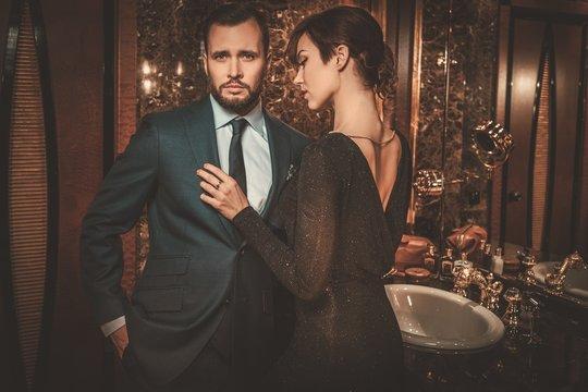 Well-dressed couple in luxury bathroom interior.