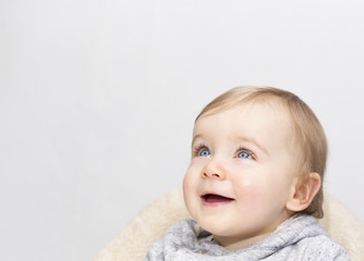 Adorable baby boy looking up on grey background