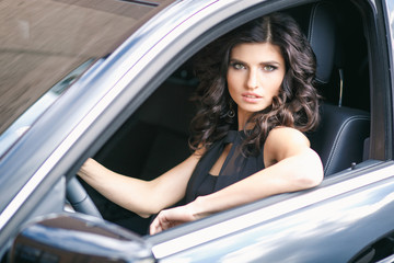 Close-up portrait of gorgeous young brunette woman driving an expensive car