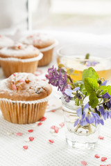 Blue spring flowers viola, muffins and cup of green tea