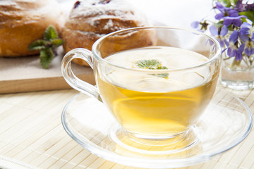 Cup of green tea with lemon balm and tasty rolls