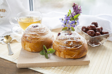 Tasty rolls with with lemon balm on wooden board
