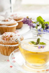 Cup of green tea with lemon balm and tasty muffins with sugar hearts