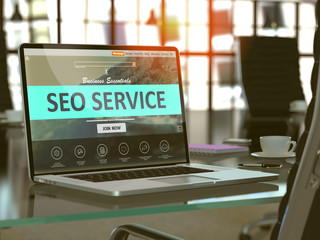 SEO - Search Engine Optimization - Service Concept. Closeup Landing Page on Laptop Screen  on background of Comfortable Working Place in Modern Office. Blurred, Toned Image. 3D Render.
