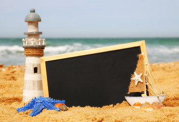 starfish, sailboat, lighthouse and chalkboard, on sea sand and ocean horizon
