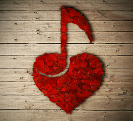 Red rose petals arranged in shape of heart with a music note inside isolated on wooden table. Love music concept