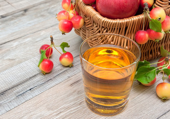 glass of apple juice and a basket of apples