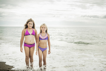 Girls smiling in waves on beach
