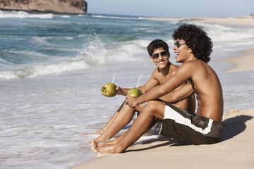 Men drinking from coconuts on beach