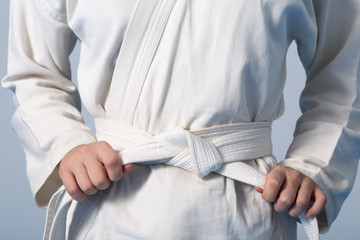 Foto auf AluDibond Kampfsport Hands tightening white belt on a teenage dressed in kimono for martial arts