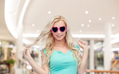 happy young woman in heart shape sunglasses