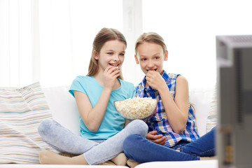 happy girls with popcorn watching tv at home