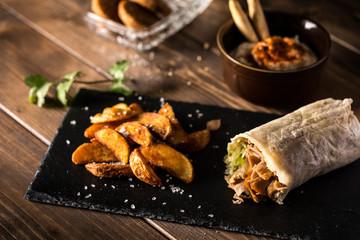 Shawarma with fried potato on table