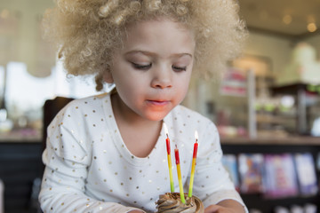 Mixed race girl blowing candles on cupcake