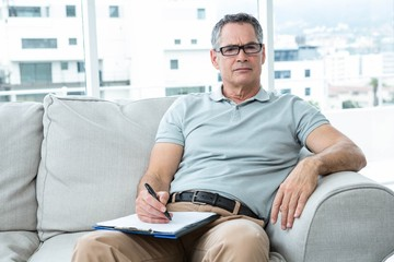 Man sitting on sofa and writing on notepad