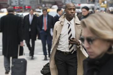 Black businessman using cell phone on city street