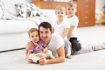 Family concept. Father with sons are playing in the room