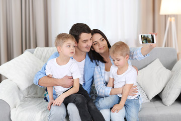 Family concept. Mother, father and sons take selfie in the room