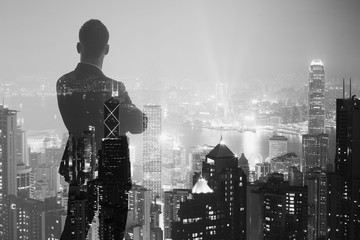 Photo of stylish adult businessman wearing trendy suit and looking night city. Double exposure, panoramic view contemporary City background. Horizontal, bokeh, blurred. Black ,white
