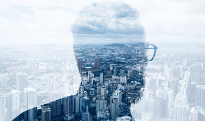 Photo of stylish bearded banker wearing trendy suit and looking city. Double exposure, panoramic view contemporary megalopolis background. Space for your business message. Wide