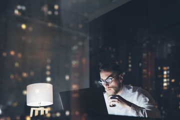 Bearded young businessman working on modern loft office at night. Man using contemporary notebook texting message, holding cup espresso, blurred background. Horizontal, film effect, bokeh Wall mural