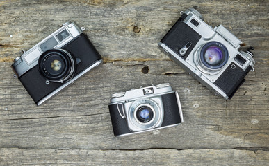 Old analog cameras on wooden surface