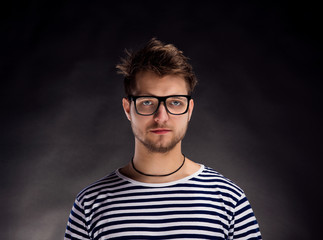 Man in striped t-shirt and eyeglasses against black background.