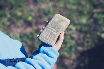 Kid hand holding a stone mobile phone.