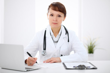 Woman doctor filling up medical history at the desk