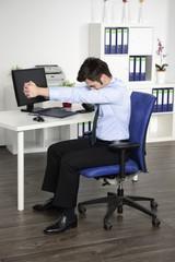 Junger Manager macht Yoga am Arbeitsplatz im Büro
