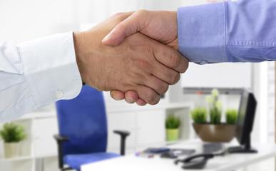 Hände beim Vertragsabschluss im Büro