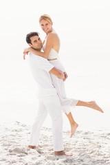 Man lifting woman on the beach