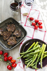 Grilled lamb with green asparagus, grill pan, red vine, wood background.