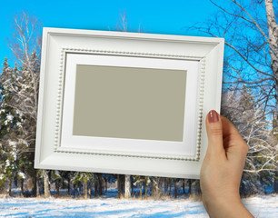 Wooden frame in woman hands. background of the Winter landscape with snow