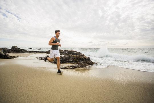 Caucasian man running on beach