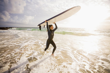 Caucasian surfer carrying board in waves